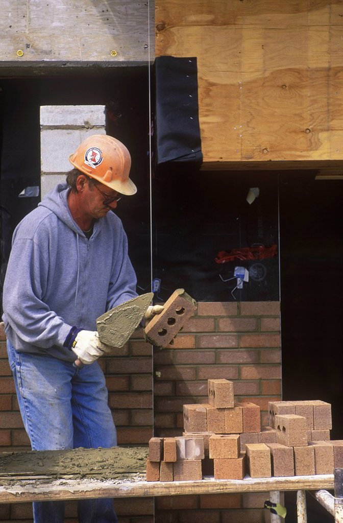 Stock Photo: 1990-22445 Construction worker  Bricklayer applies mortar while constructing brick wall, British Columbia, Canada