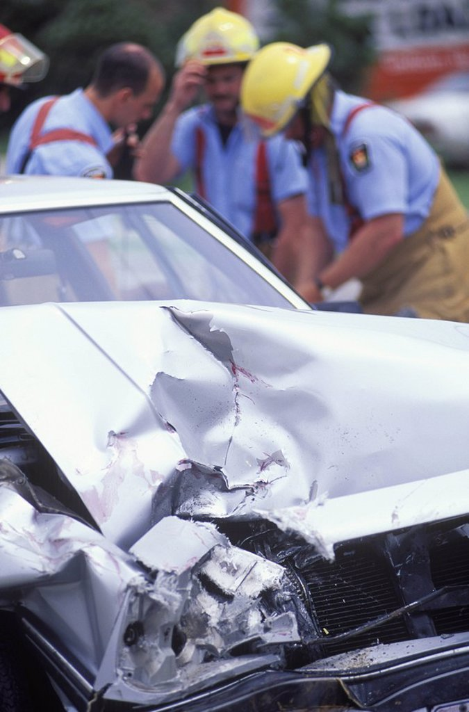 Stock Photo: 1990-22468 Auto accident - Crumpled car and out of focus emergency workers beyond, British Columbia, Canada