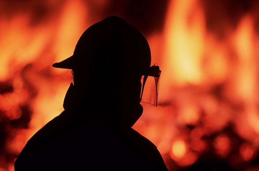 Stock Photo: 1990-23450 Silhouette of fireman with burning house beyond, British Columbia, Canada