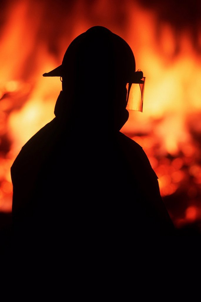 Stock Photo: 1990-23466 Silhouette of fireman with burning house beyond, British Columbia, Canada