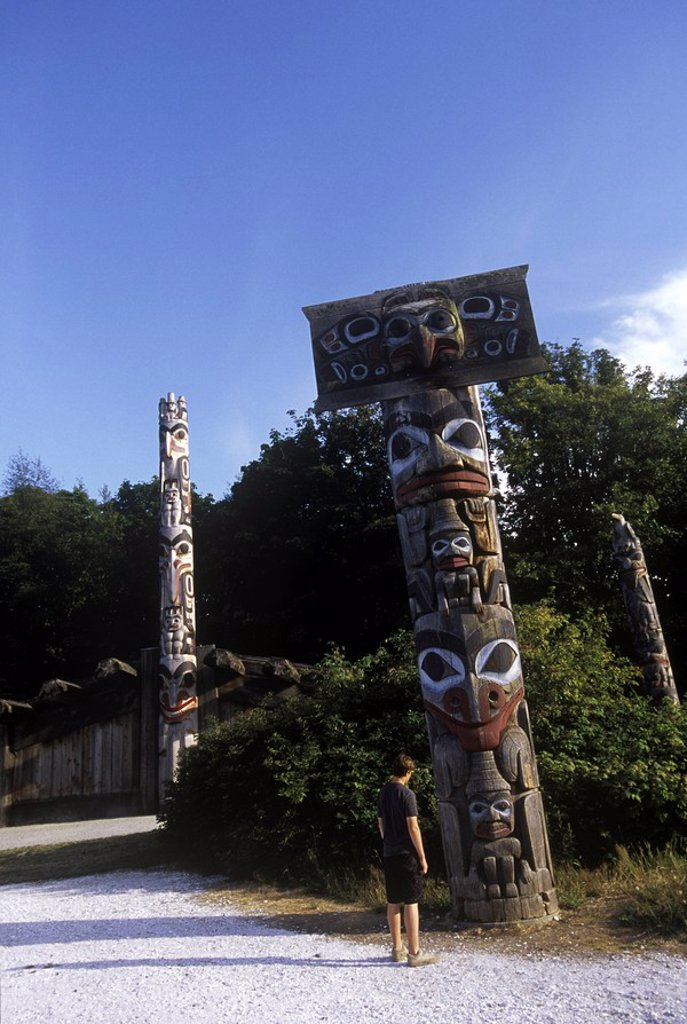 Boy looks at Totem poles on the grounds of the University of British Columbia Museum of Anthropology, British Columbia, Canada : Stock Photo