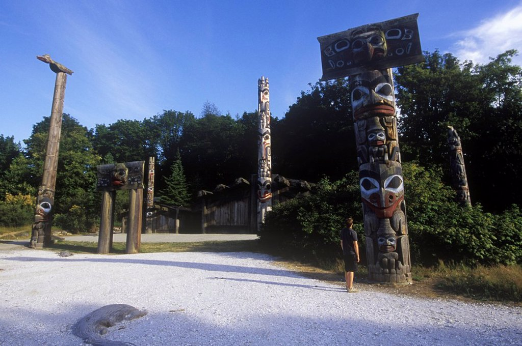 Stock Photo: 1990-24439 Boy looks at Totem poles on the grounds of the University of British Columbia Museum of Anthropology, British Columbia, Canada