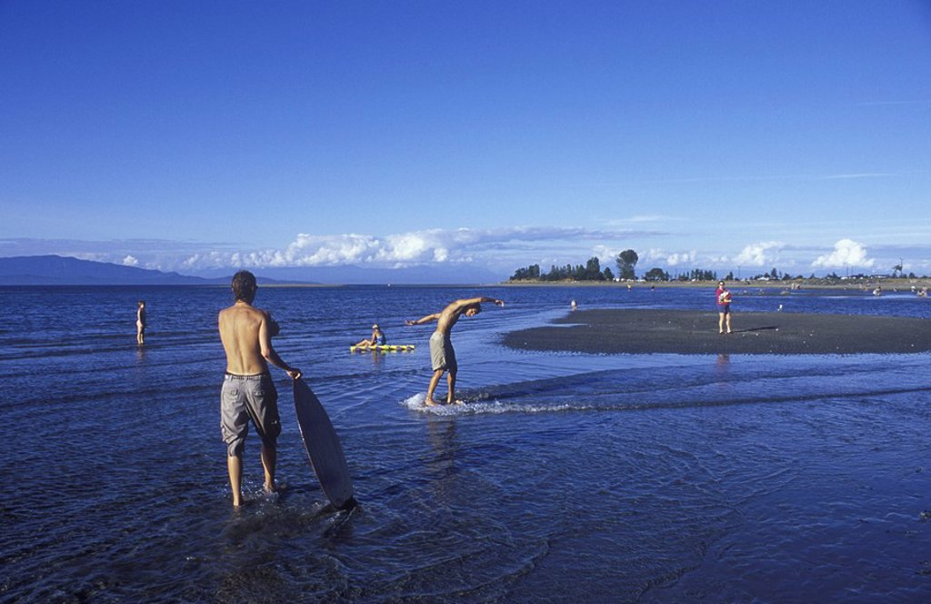 Stock Photo: 1990-24631 Parksville Beach Young men skim boarding, Vancouver Island, British Columbia, Canada