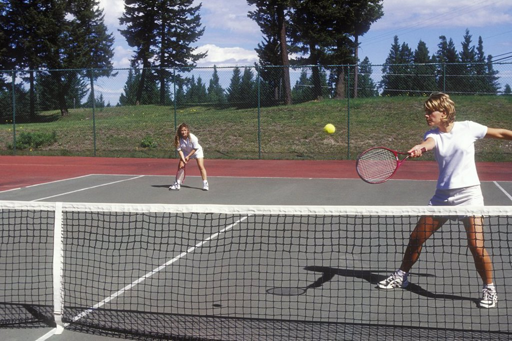 Stock Photo: 1990-25583 Two women playing doubles tennis, 108 Mile Rd, British Columbia, Canada