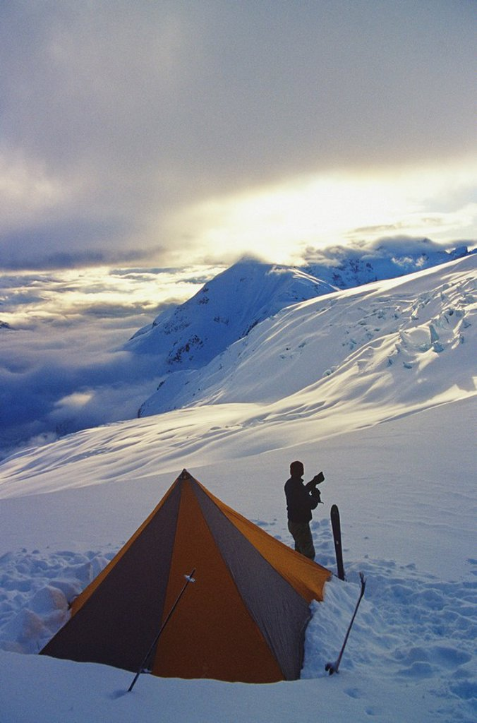 Man at sunrise on the Garibaldi Neve traverse, behind Mount Garibaldi, in Garibaldi Provincial Park, near Squamish, British Columbia, Canada : Stock Photo