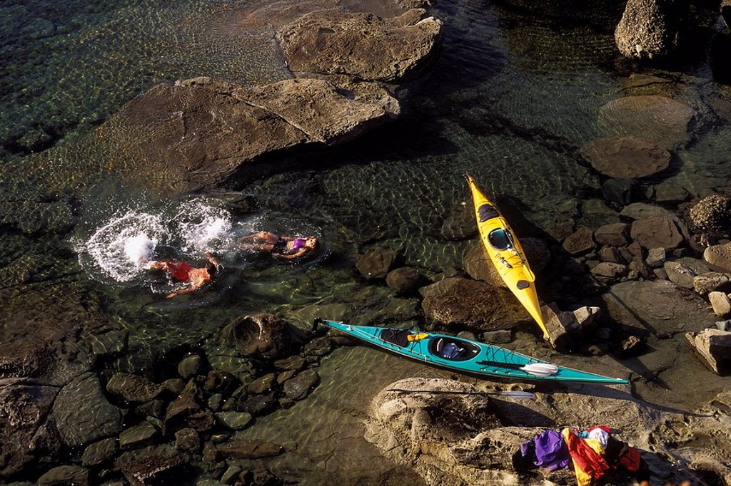 Couple camped on islet while sea kayaking, Hornby Island, British Columbia, Canada : Stock Photo