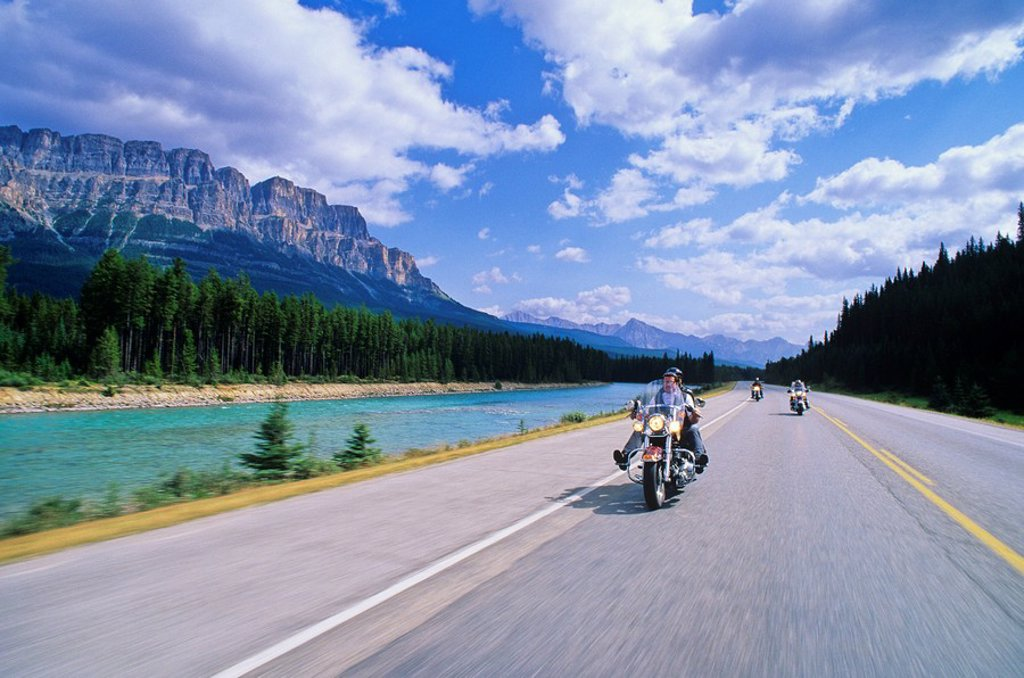 Motorcyclists along Highway One, Castle Mountain and the Bow River beyond, Alberta, Canada : Stock Photo