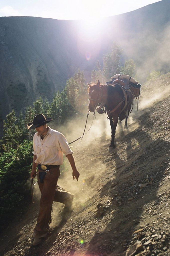 Stock Photo: 1990-28667 leading a horse in the South Chilcotin Mountains, near Gold Bridge, British Columbia, Canada