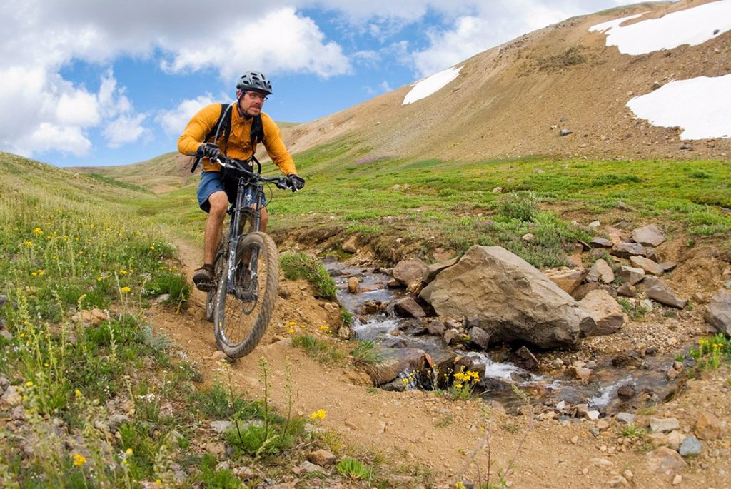 Mountain biker rides the trail down from Deer Pass, Southern Chilcotin Mountains, British Columbia, Canada : Stock Photo