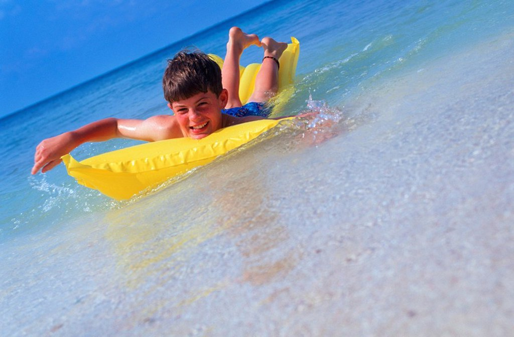 Mexico, Yucatan Peninsula, Carribean resort at Isla Mujeres, boy with float mattress : Stock Photo