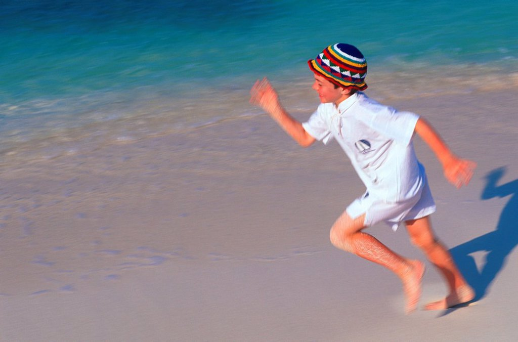 Mexico, Yucatan Peninsula, Carribean resort at Isla Mujeres, boy running on beach : Stock Photo
