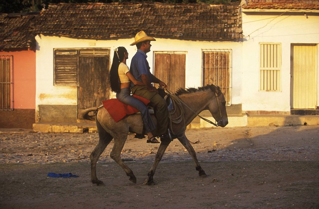 Cuba, Trinidad, man and woman travel on donkey´s back : Stock Photo