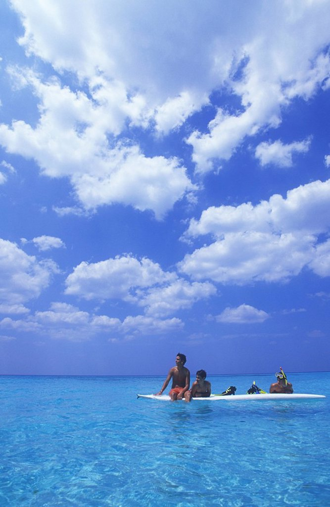 Stock Photo: 1990-29546 Cuba, Veradaro, local boys on wind surf board, cumulus cloud over azure water of carribean sea