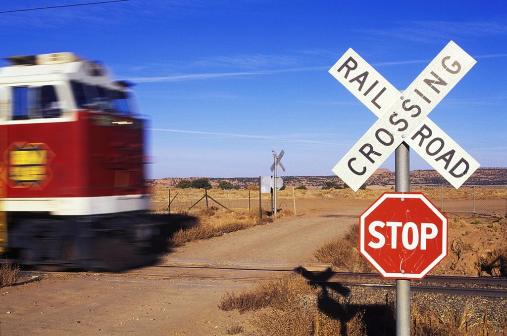 Freight train with motion blur at level crossing with railway sign : Stock Photo