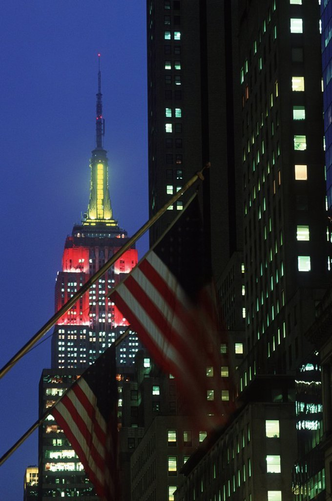 Stock Photo: 1990-30216 USA, New York City, Empire State Building , with flags at dusk