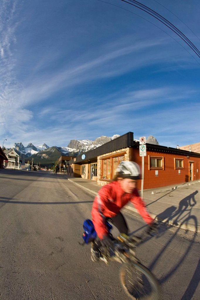 Stock Photo: 1990-32713 A young woman commuting on her bike in Canmore, AB