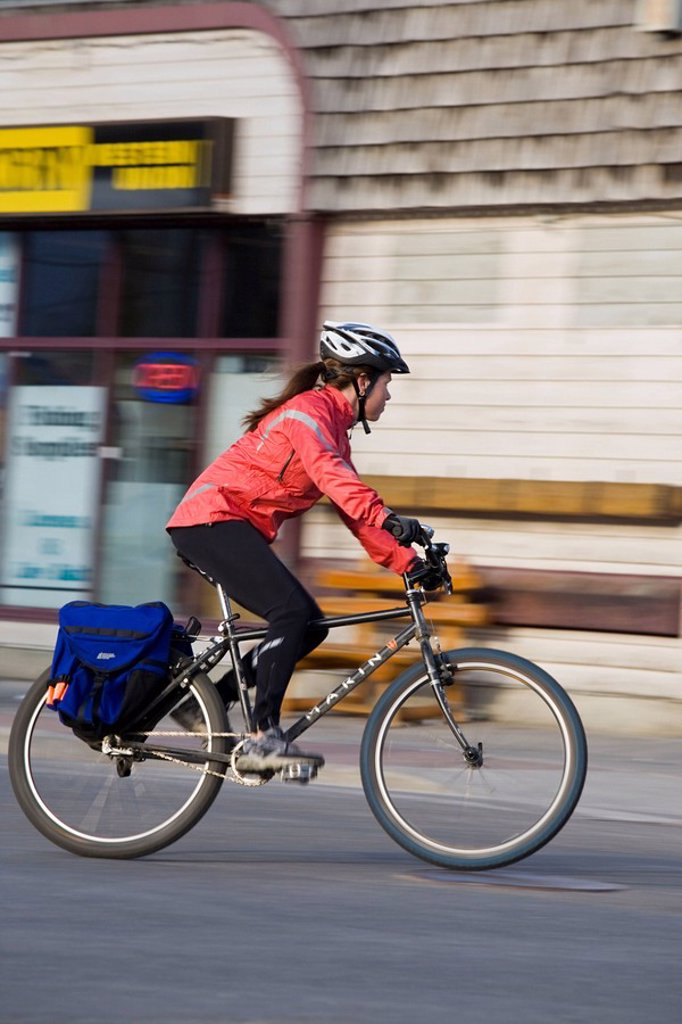 Stock Photo: 1990-32714 A young woman commuting on her bike in Canmore, AB