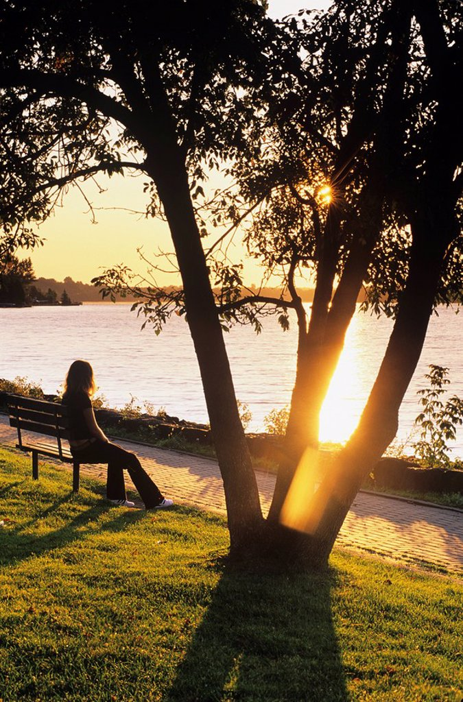 Young lady sitting on park bench in Bell Park near Ramsey lake at sunrise, sudbury, ontario, Canada : Stock Photo