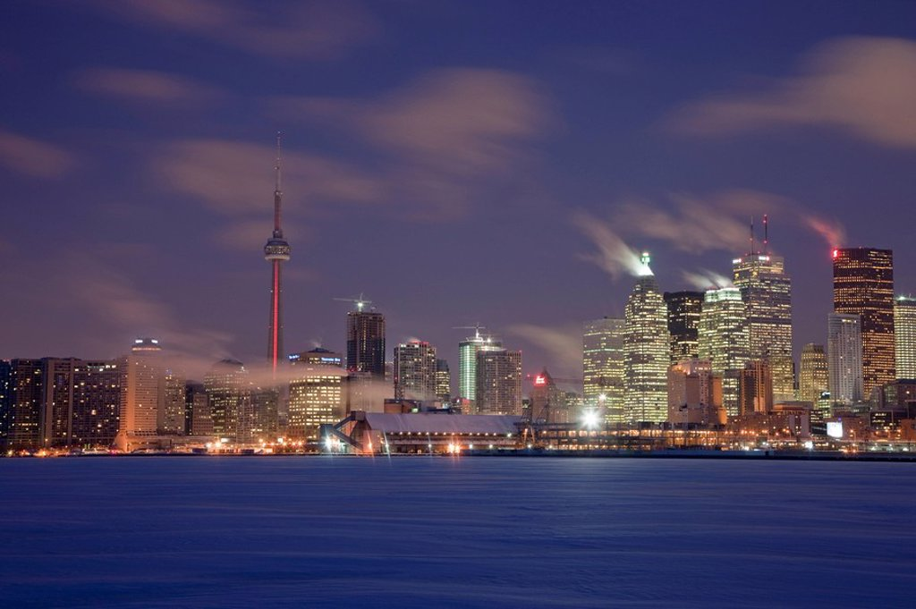 A winter skyline of Toronto Ontario Canada with red lights shining on the CN Tower and just before dawn : Stock Photo