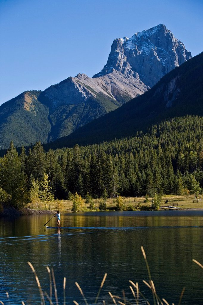Stock Photo: 1990-33877 A young asian woman uses her paddle board on a small lake in Canmore, AB