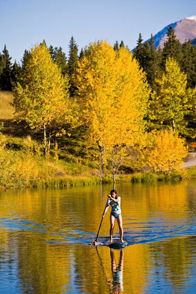 Stock Photo: 1990-33878 A young asian woman uses her paddle board on a small lake in Canmore, AB