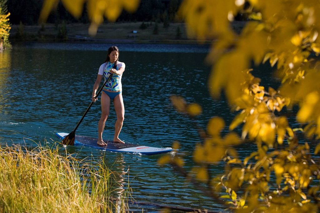 Stock Photo: 1990-33880 A young asian woman uses her paddle board on a small lake in Canmore, AB
