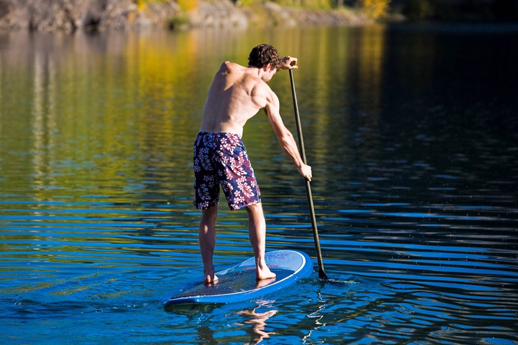 Stock Photo: 1990-33881 A young man paddleboards on Quarry lake in Canmore, AB
