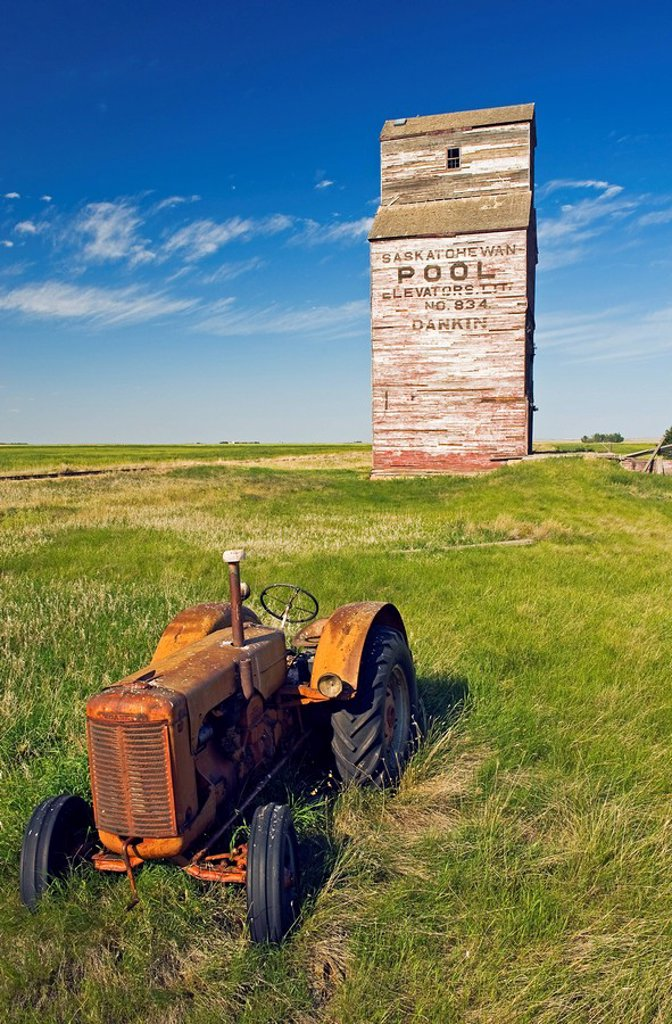 old tractor with abandoned elevator in the background, Dankin, Saskatchewan, Canada : Stock Photo