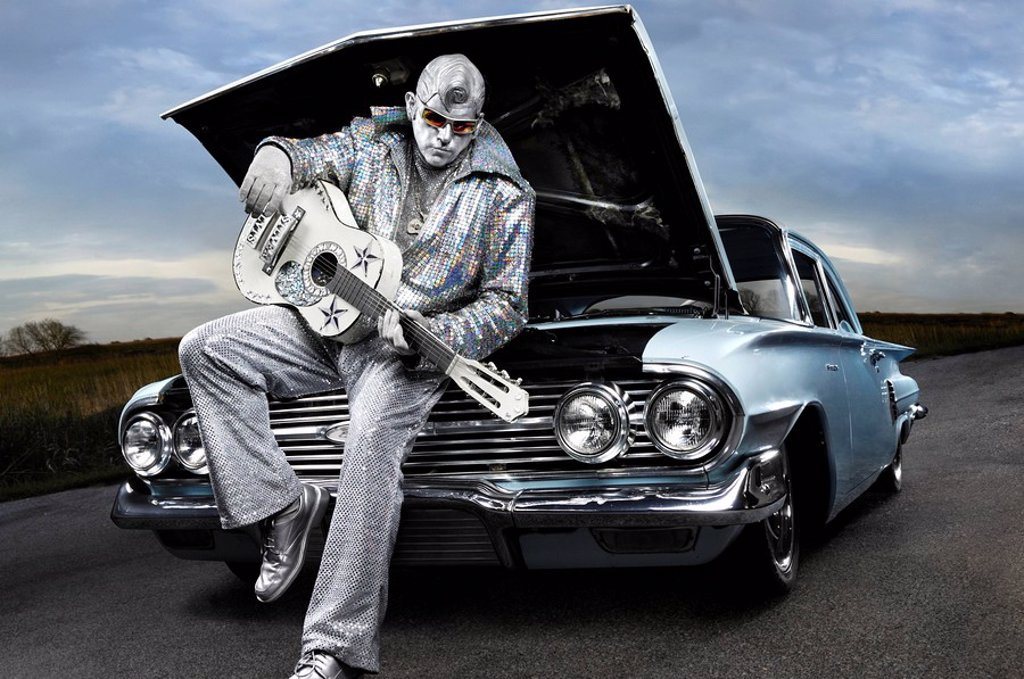 Rock´n´roll symbol Silver Elvis with a guitar sitting on a broken down classic car with open hood. Performing artist Peter Jarvis from Toronto Canada. : Stock Photo