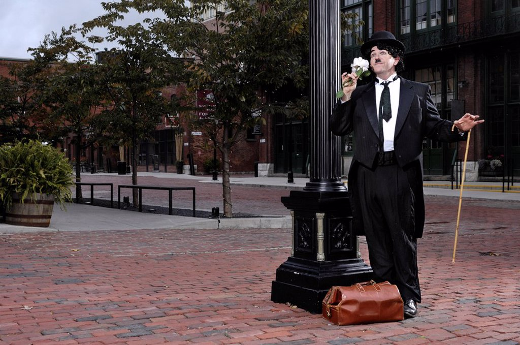 Charlie Chaplin mime standing on the street with flower in hand with romantic expression. Artistic performance humorous concept. Performing artist Peter Jarvis. The Distillery Toronto Canada. : Stock Photo