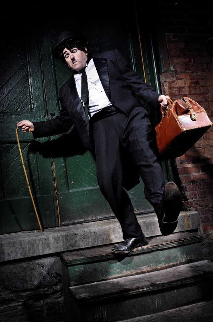 Stock Photo: 1990-35422 Man in a black suit with a bag Charlie Chaplin mime tripping and falling from a staircase. Artistic performance humorous concept. Performing artist Peter Jarvis. Toronto Canada.