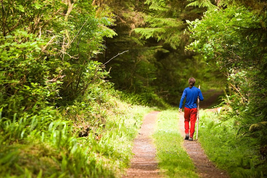 Stock Photo: 1990-35547 A young hiker strolls along a path, Ronning Garden, Holberg, Northern Vancouver Island, British Columbia, Canada.