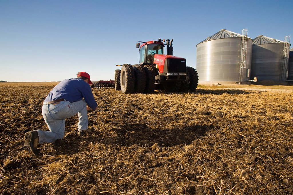 Stock Photo: 1990-36738 a man examines newly cultivated soil with tractor pulling cultivating equipment and grain storage bins in the background, near Lorette, Manitoba, Canada