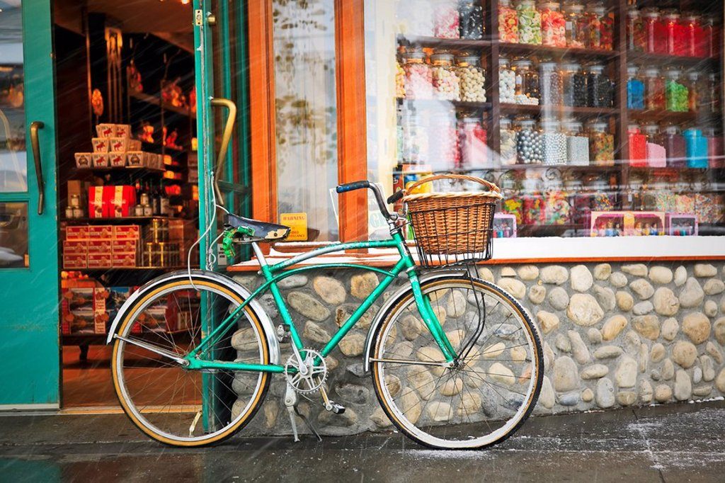 Stock Photo: 1990-37465 Cruiser bicycle with basket parked outside a Candy Store during a snowfall. Banff, Alberta, Canada.