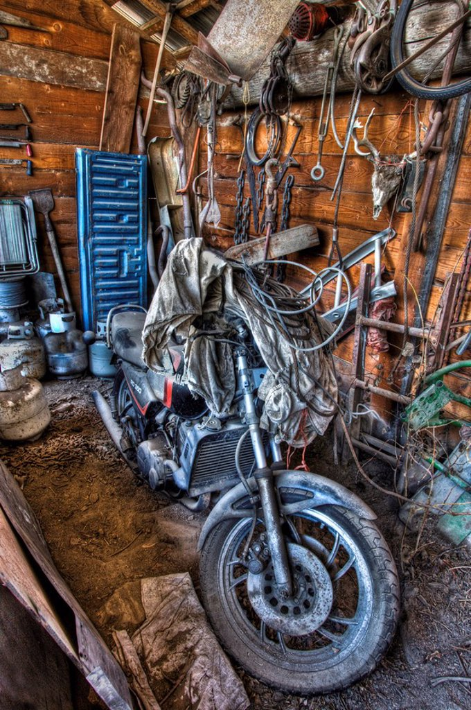 Close up of a dusty motorcycle in a storage barn. : Stock Photo