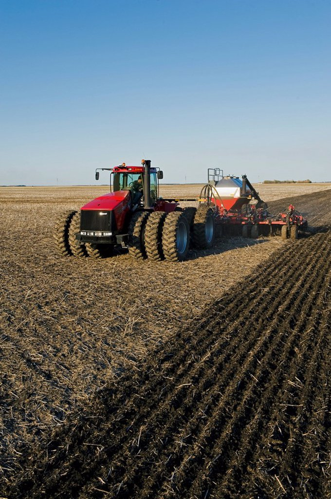 moving tractor and and air till seeder planting grain, near Dugald, Manitoba, Canada : Stock Photo