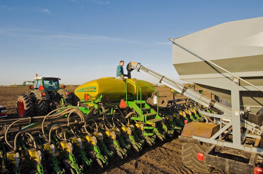 a farmer loads a seeder tank with soybean seed, near Lorette, Manitoba, Canada : Stock Photo