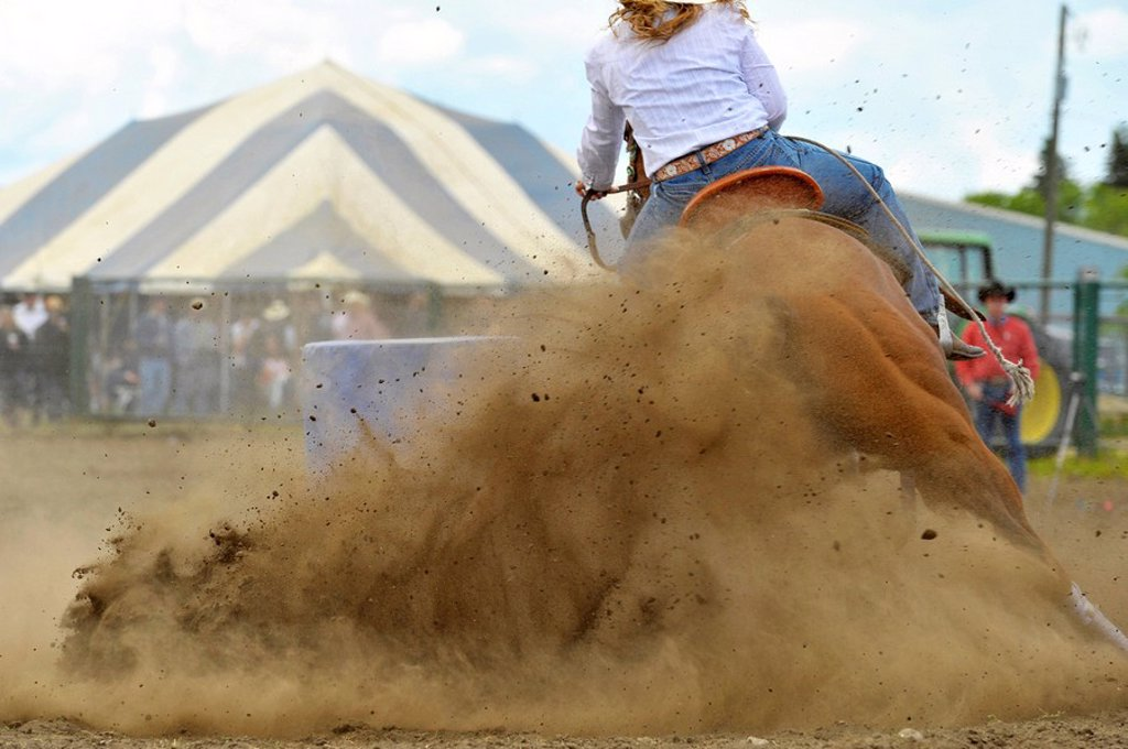 Stock Photo: 1990-39844 A rodeo rider competing in a barrel racing event under dusty arena conditions.