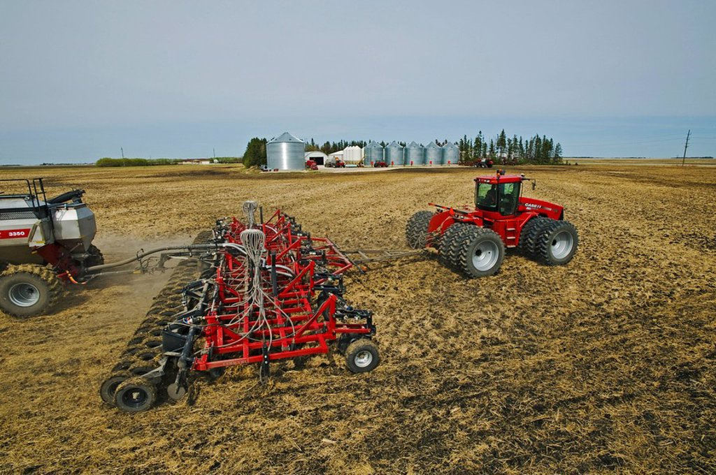 moving tractor and and air till seeder planting canola in wheat stubble, farmyard in the background, near Dugald, Manitoba, Canada : Stock Photo
