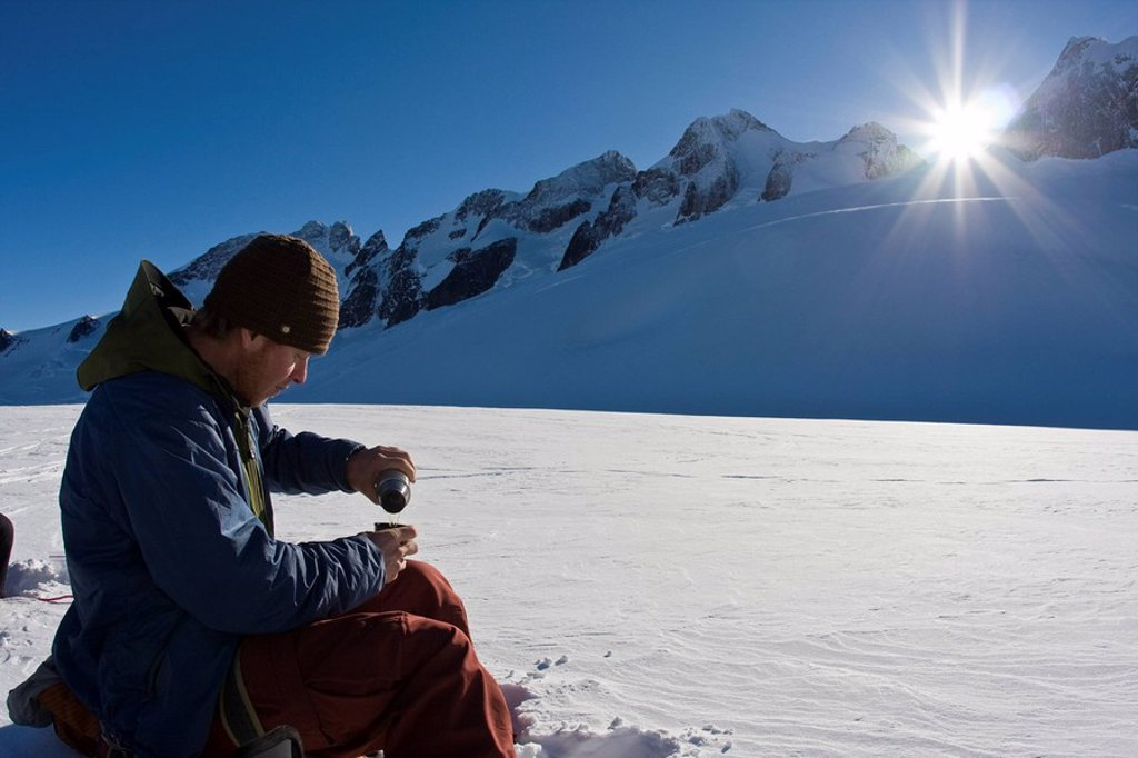 A man takes a lunch break while splitboarding in Fairy Meadows, Selkirks, BC : Stock Photo