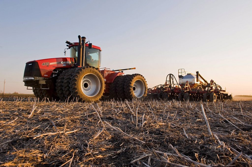 moving tractor and and air till seeder planting grain in canola stubble, near Dugald, Manitoba, Canada : Stock Photo