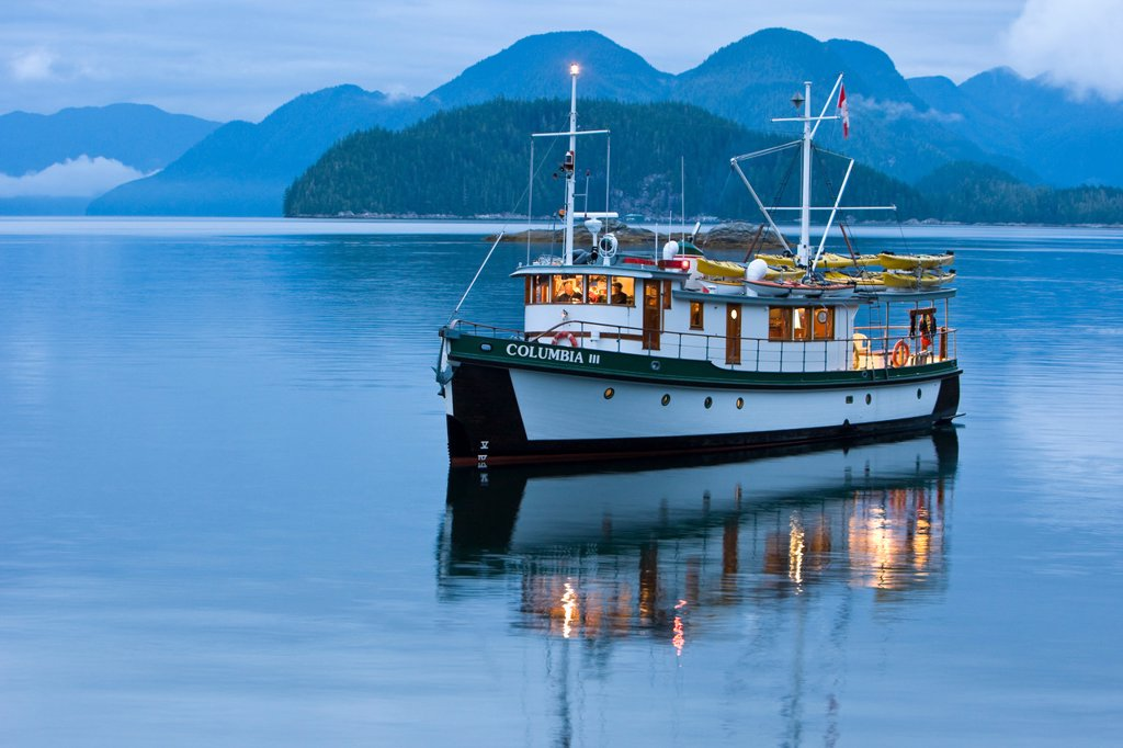 The MV Columbia III anchored for the night within the Broughton Archipelago exudes a warmth from interior lighting as evening sets in. Broughtin Archipelago, Central British Columbia Coast, Canada. : Stock Photo