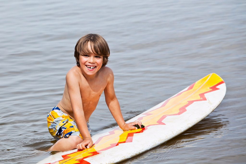 Young happy boy playing in water on a surfboard. Lake Winnipeg, Gimli, Manitoba, Canada. : Stock Photo