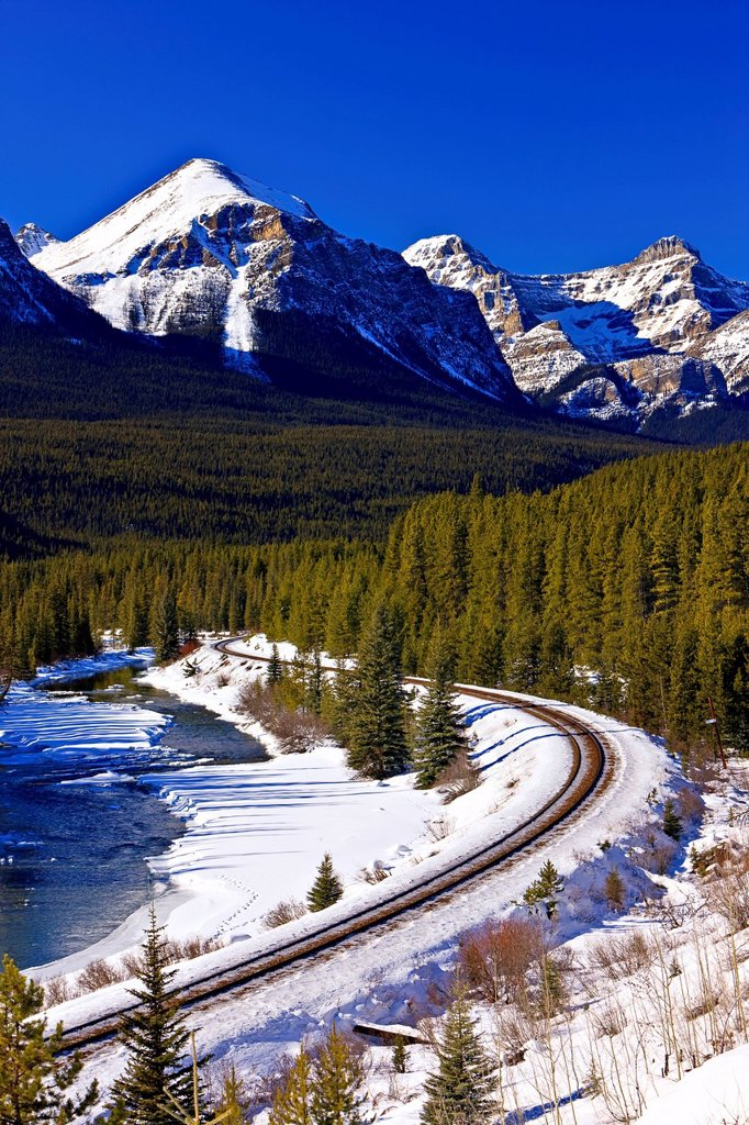 Railway tracks beside the snow and ice fringed Bow River during winter with Fairview Mountain 2743 metres/9001 feet in the background, Banff National Park, Canadian Rocky Mountains, Alberta, Canada. : Stock Photo