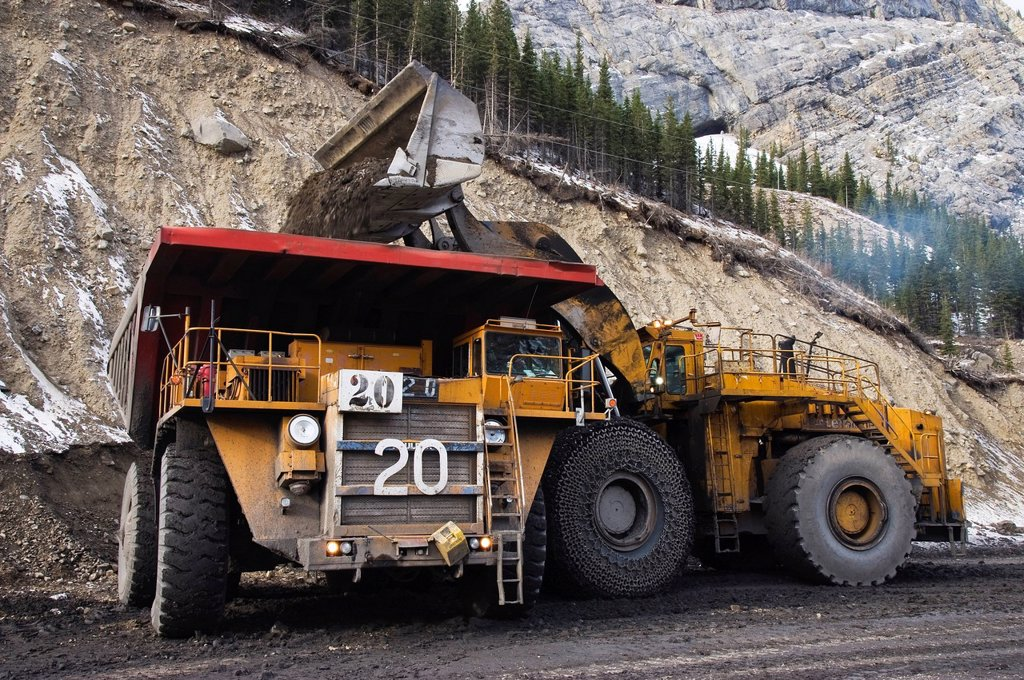 A large bucket loader loading soil into an off road haul truck at a coal mine site, Alberta, Canada. : Stock Photo
