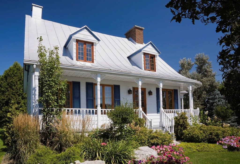 Stock Photo: 1990-46332 Old Canadiana circa 1821 cottage style wooden siding Residential Home with landscaped front yard, Quebec, Canada.