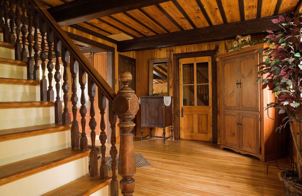 Stock Photo: 1990-46358 Pinewood stairs, armoire and cabinet in the living room of an Old Canadiana 1826 cottage style fieldstone Residential Home undergoing renovations, Quebec, Canada.