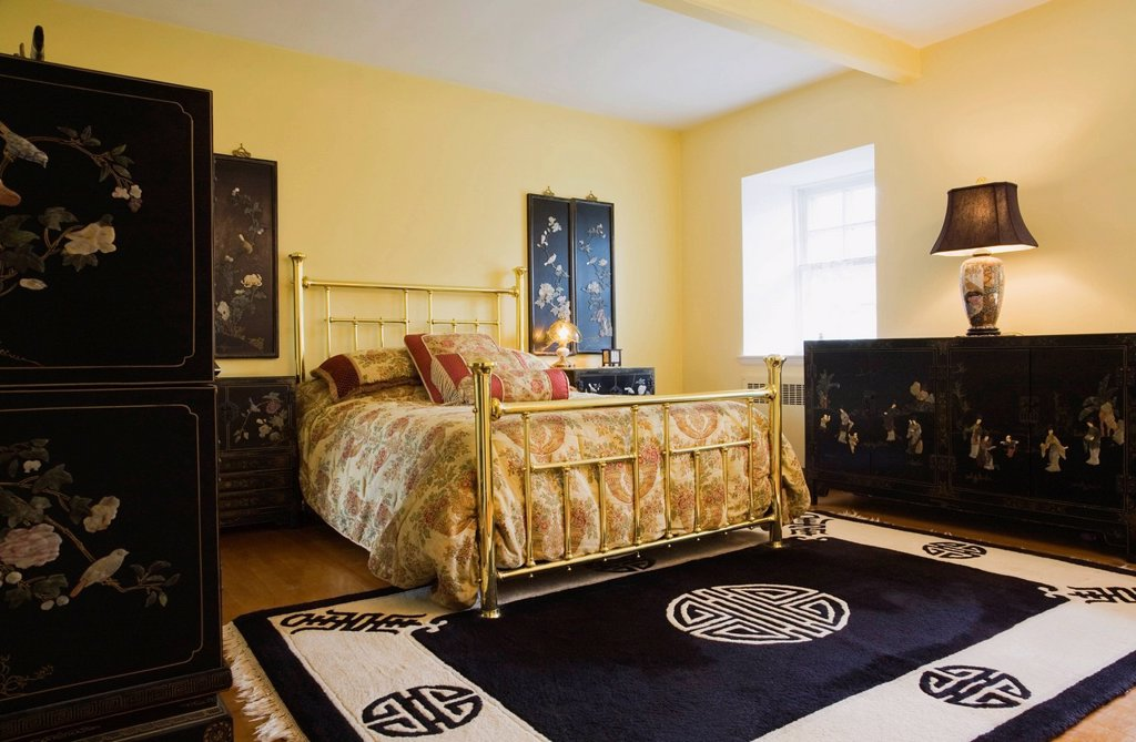 Stock Photo: 1990-46373 Master bedroom with brass bed, chinese furniture and furnishings on the upstairs floor of an Old circa 1834 Residential fieldstone and wooden siding home, Quebec, Canada,