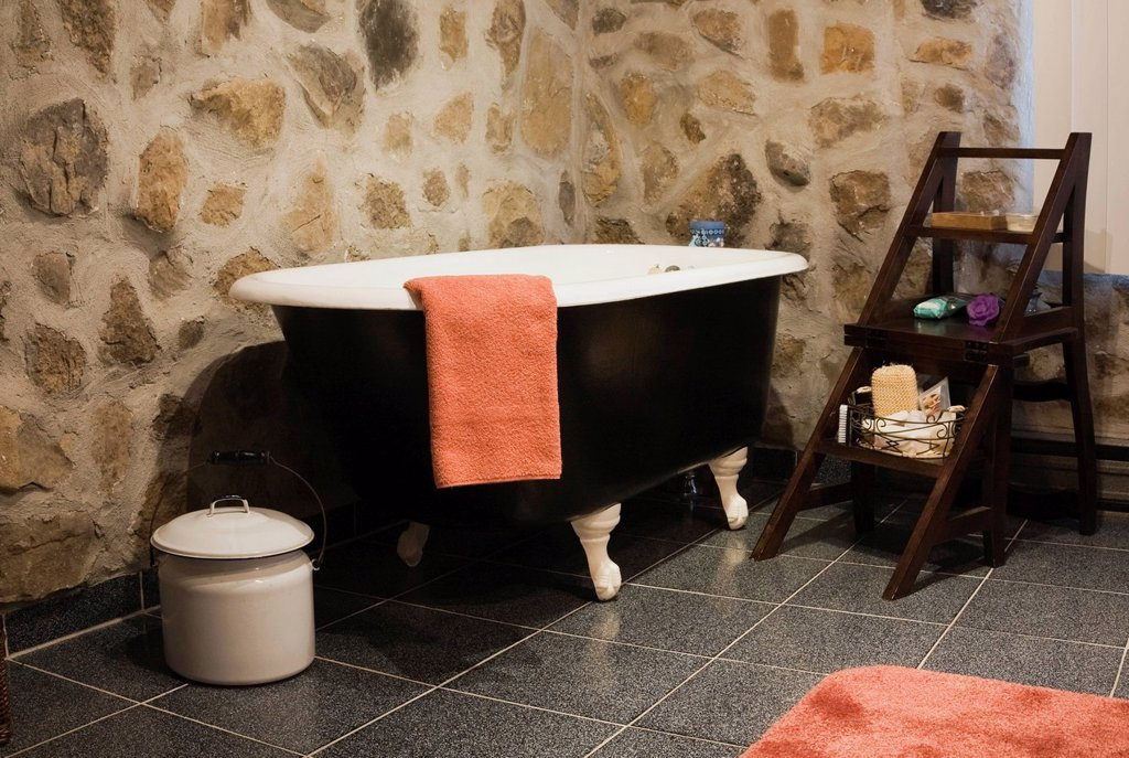 Stock Photo: 1990-46381 Bathroom with a roll top bathtub and antique furnishings in a 1978 reproduction of an old Canadiana cottage style log and fieldstone residential home, Quebec, Canada.