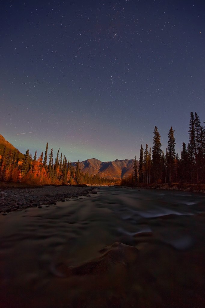 Wheaton River at night with meteor shooting above mountains. Faint aurora seen as well. Yukon, Canada. : Stock Photo